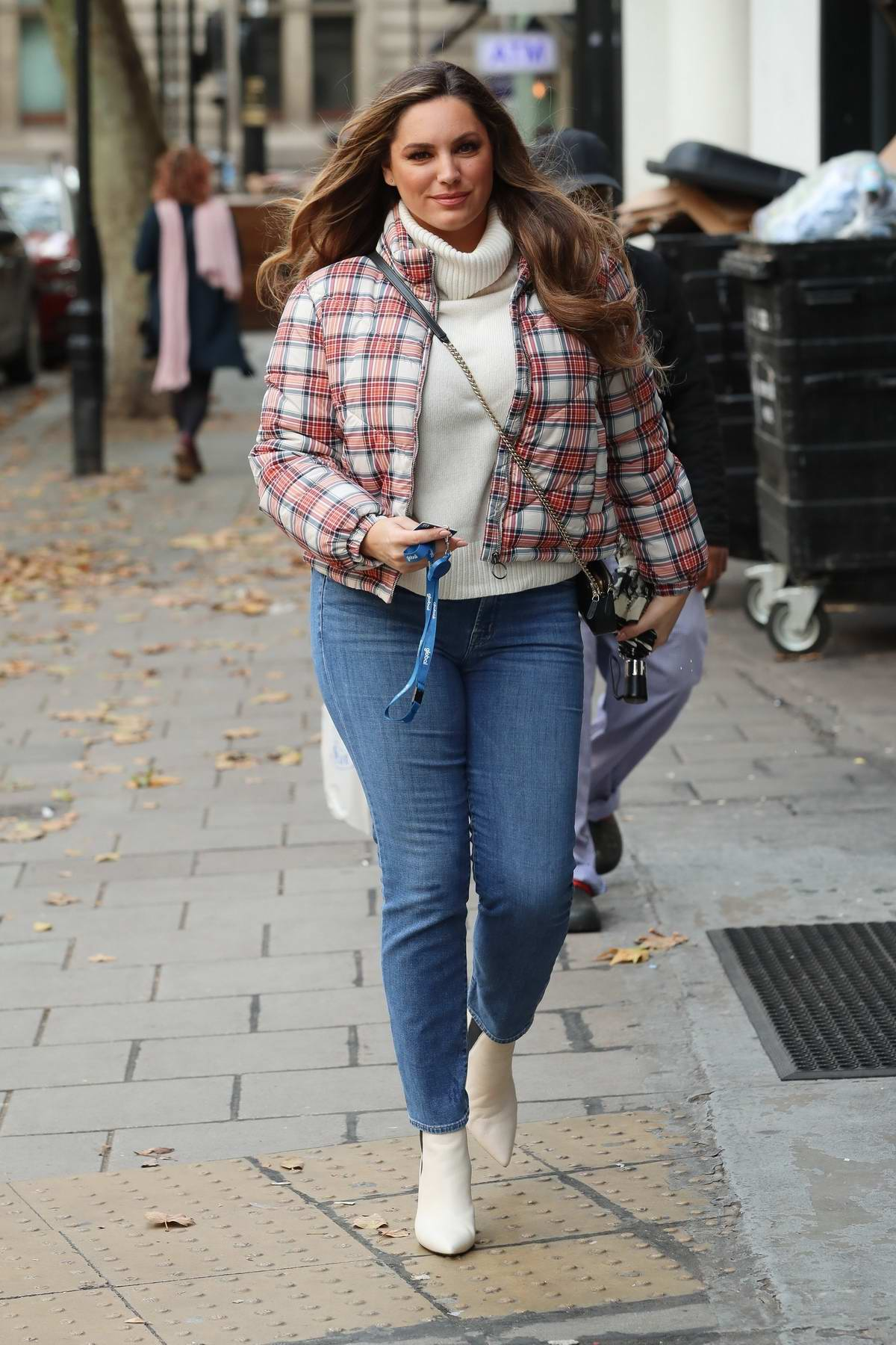 Kelly Brook wears a cream turtleneck sweater with plaid jacket as she arrives at Global Radio Studios in London, UK