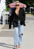 Khloe Kardashian wears a plunging black shirt and jeans as she steps out for lunch at Stanley's in Sherman Oaks, California