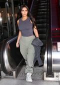Kim Kardashian wears a grey tank top and olive green pants as she steps out for lunch in Calabasas, California