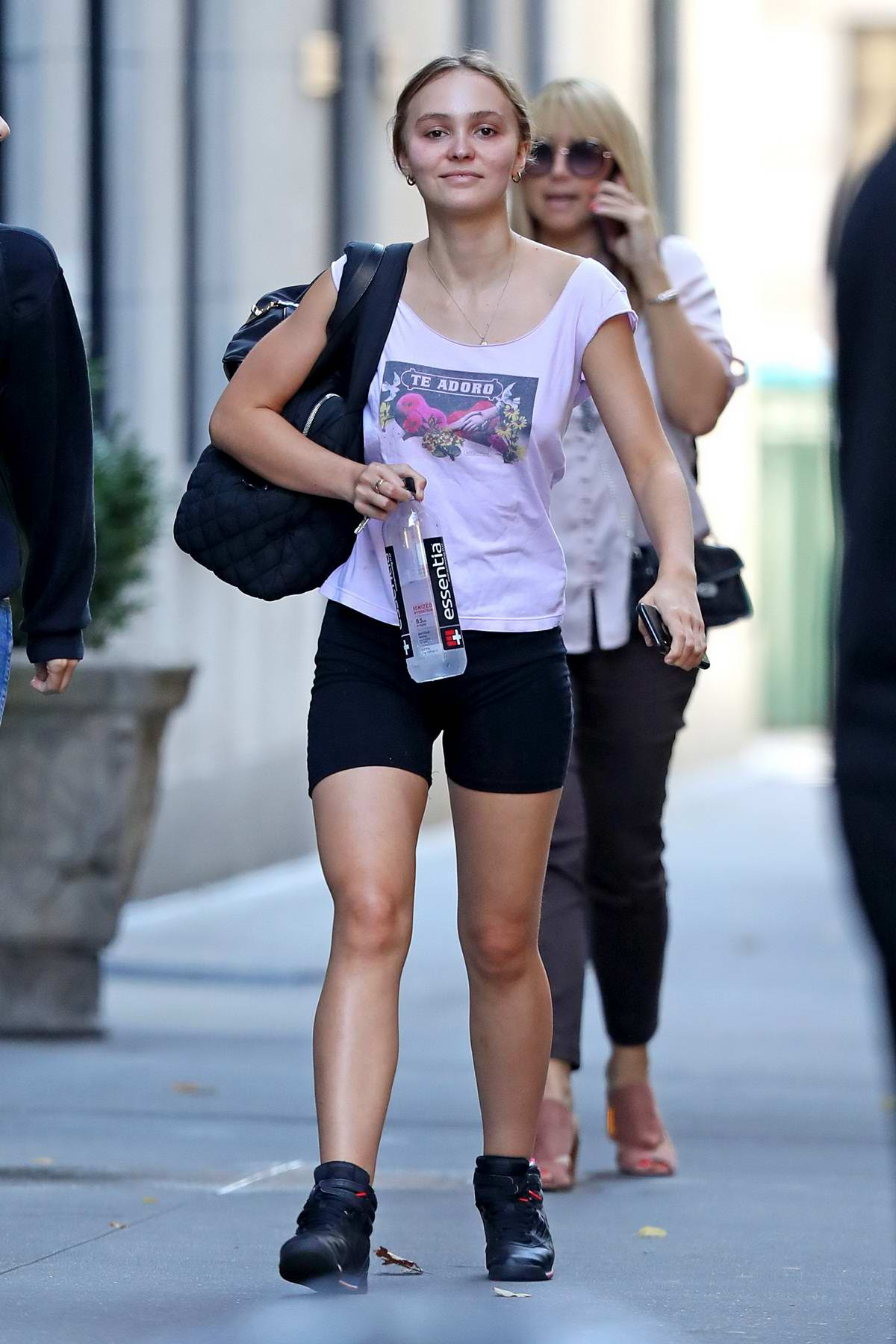 Lily-Rose Depp wears a graphic print top and black shorts while stepping out after a workout session in New York City