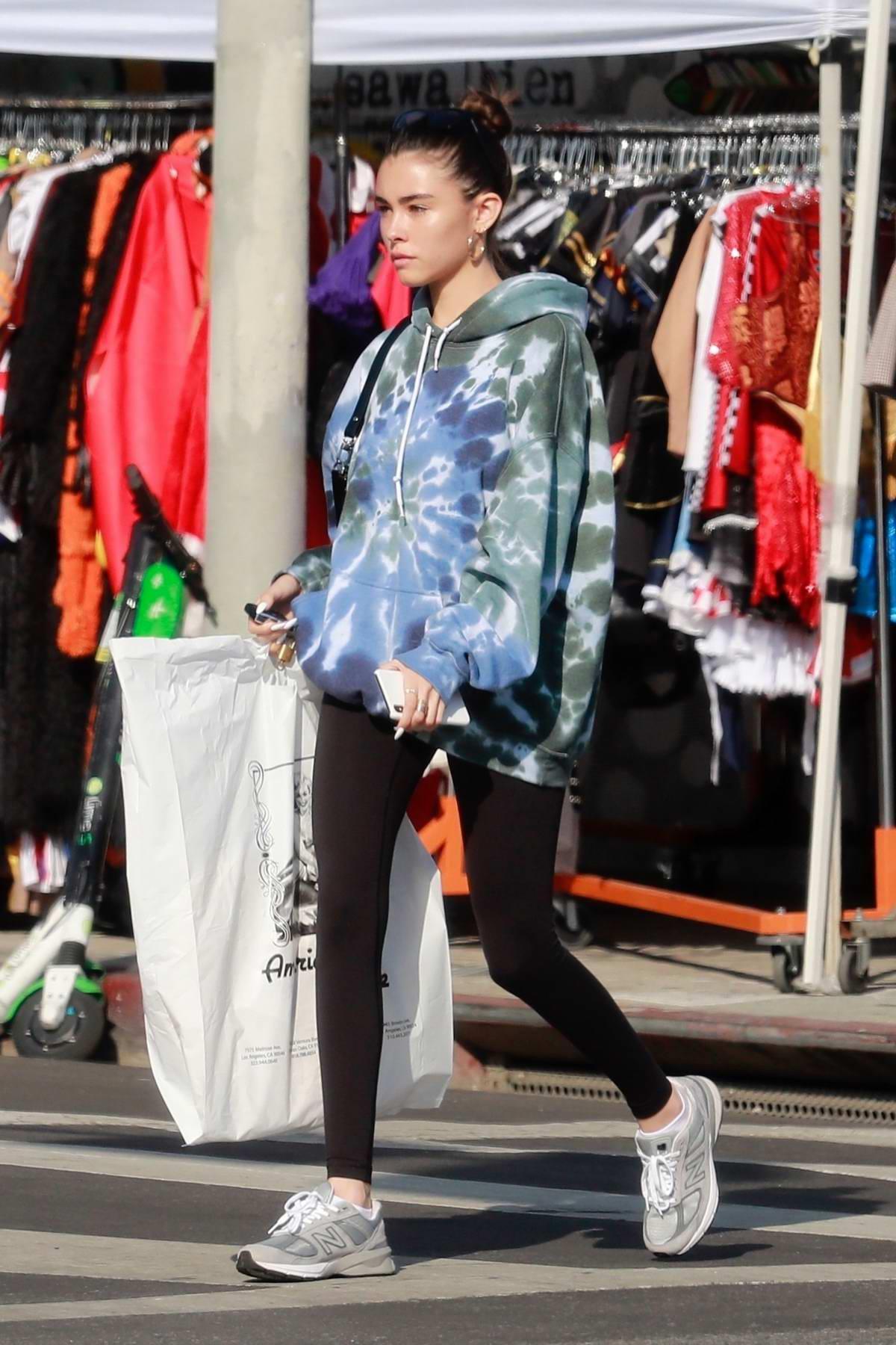 Madison Beer wears a tie-dye hoodie and black leggings during a shopping trip to American Vintage in Los Angeles
