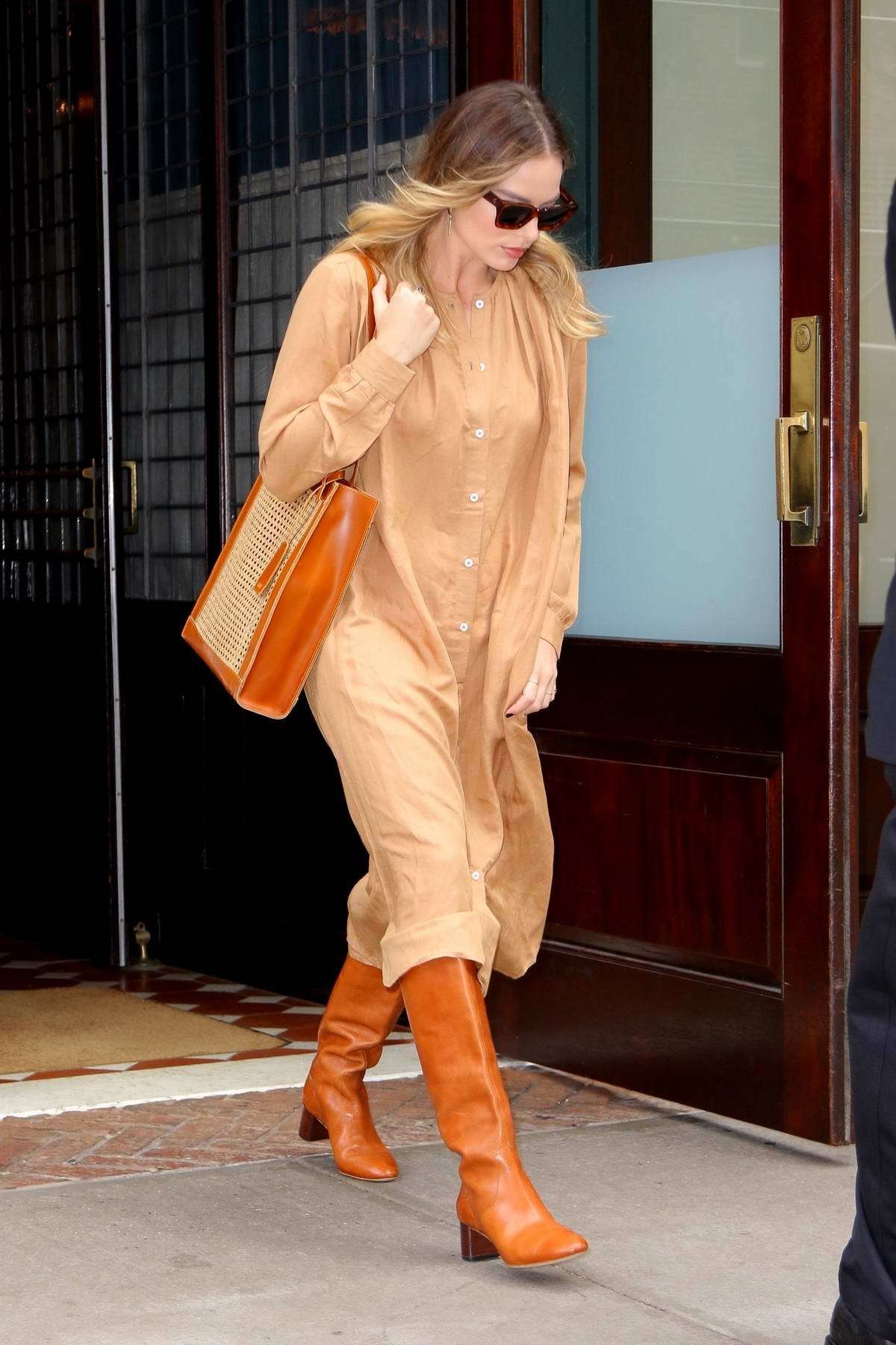 Margot Robbie wears a buttoned down beige dress and burnt orange leather boots as she leaves her hotel in New York City
