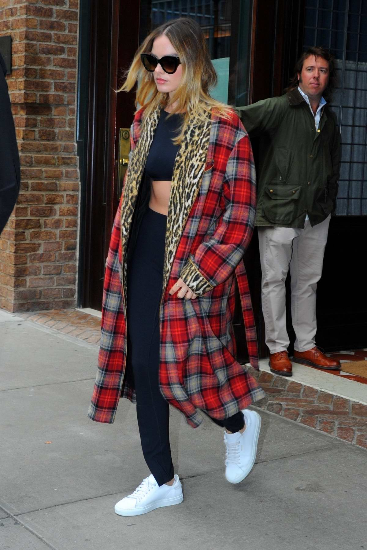 Margot Robbie wears a plaid overcoat over a black crop top and leggings as she leaves her hotel in New York City