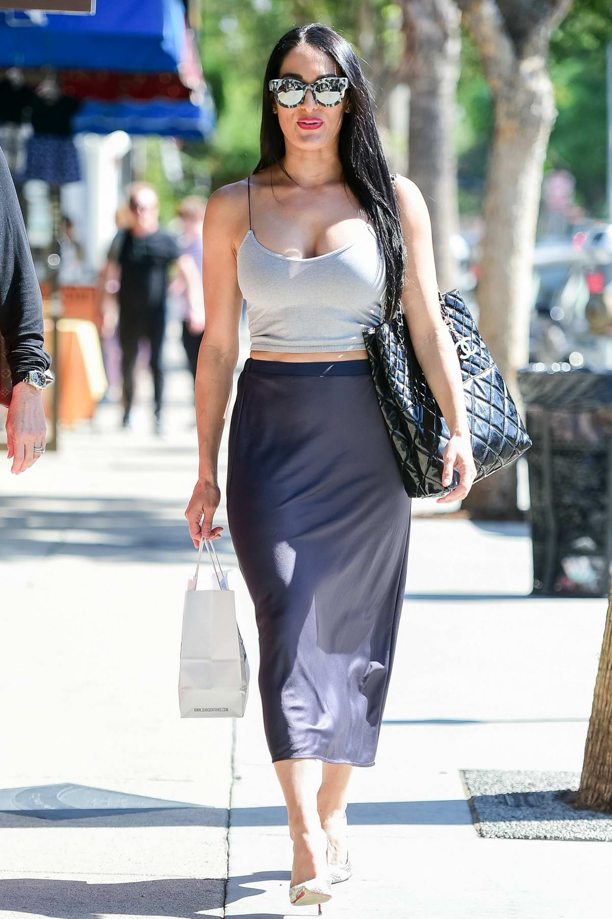 Nikki Bella rocks a grey crop top and blue silk skirt as she steps out for coffee with a friend in Los Angeles