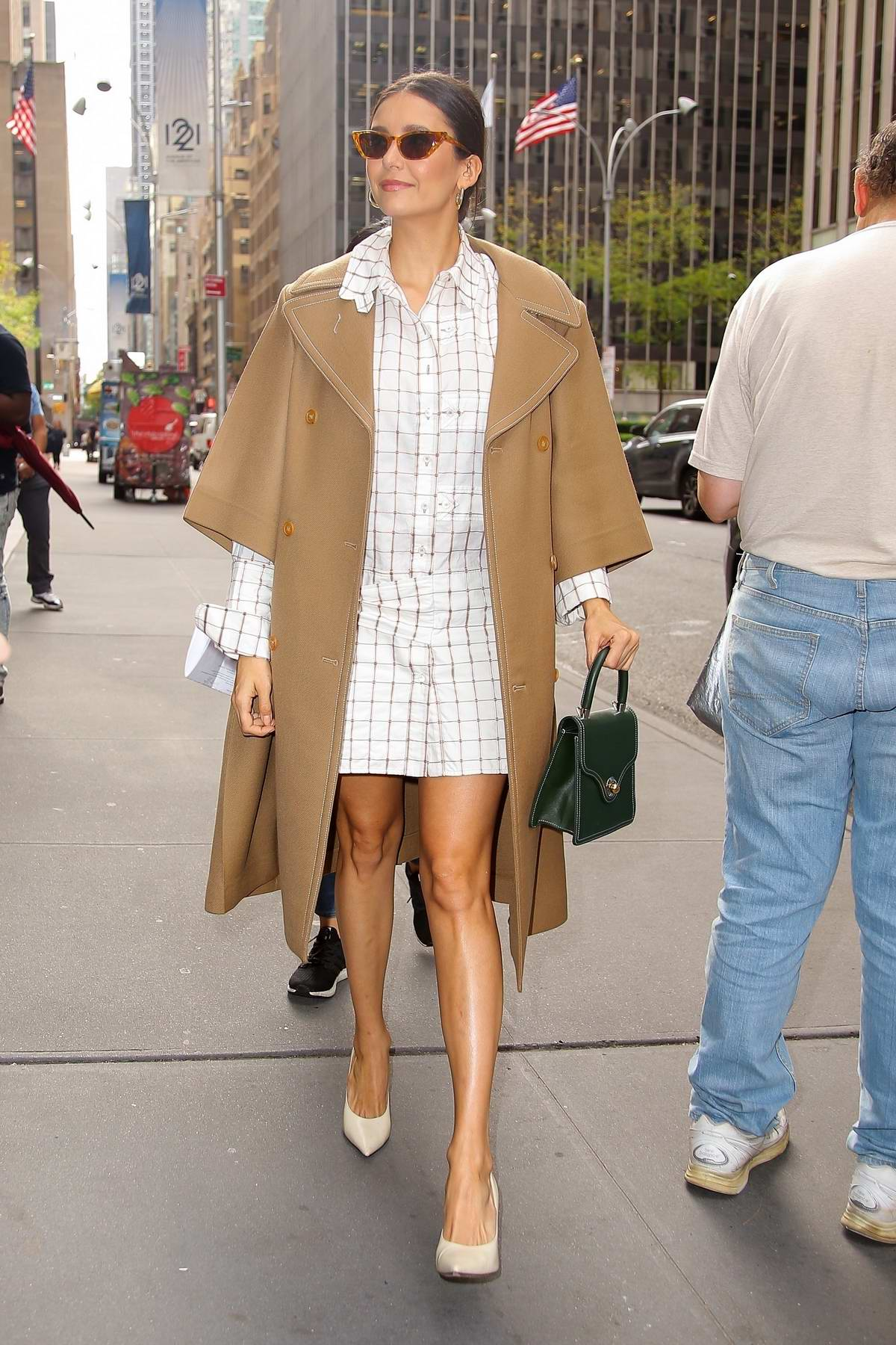 Nina Dobrev looks stylish in a checkered white dress and brown trench coat while visiting SiriusXM Studios in New York City