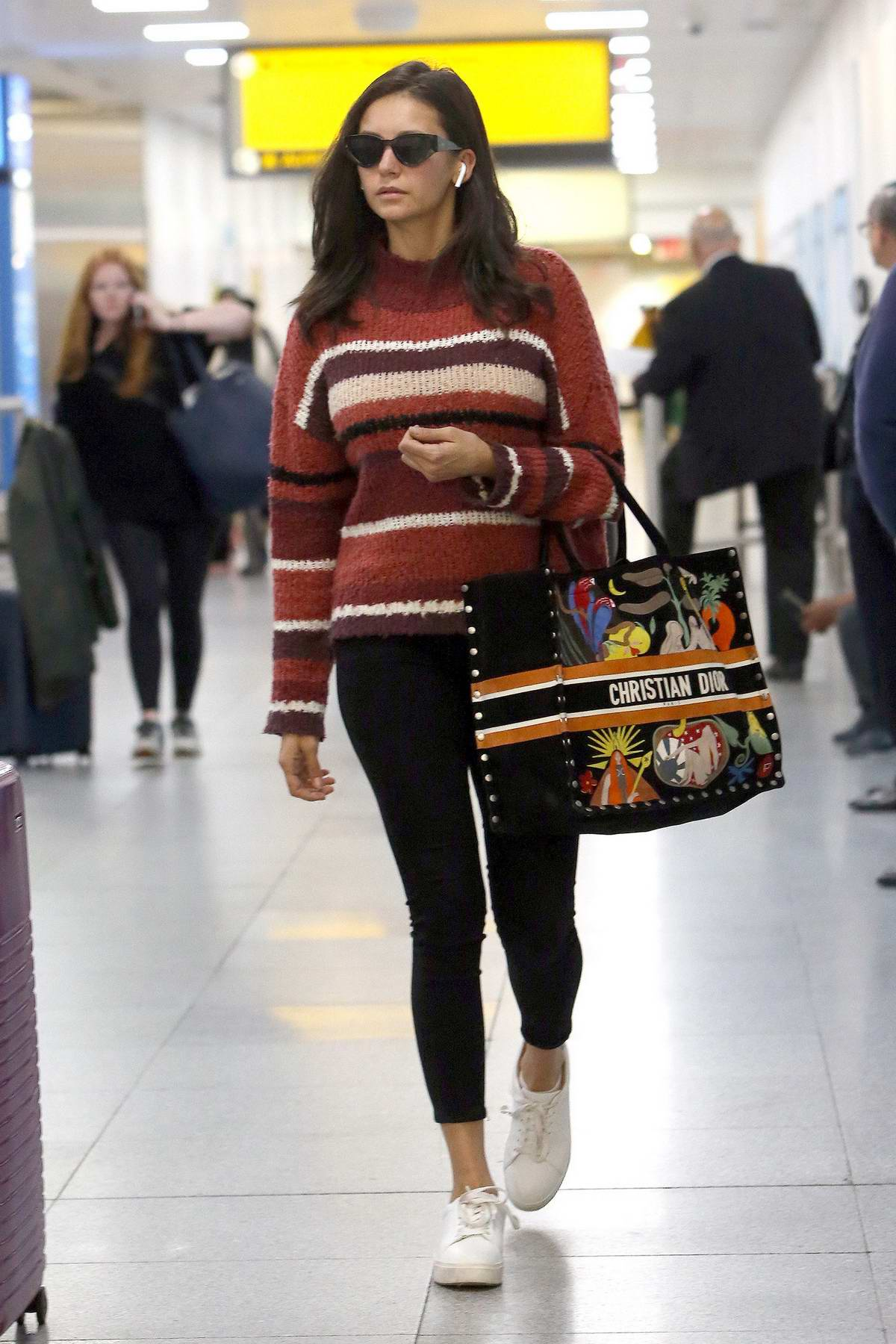 Nina Dobrev spotted in a striped sweater and black leggings as she touches down at JFK Airport in New York City
