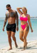 Olivia Buckland wears a hot pink bikini as she hits the beach with Alex Bowen in Dubai, UAE