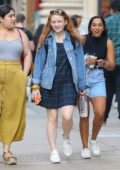 Sadie Sink wears a plaid dress, denim jacket and sneakers while out for a stroll with some friends in New York City