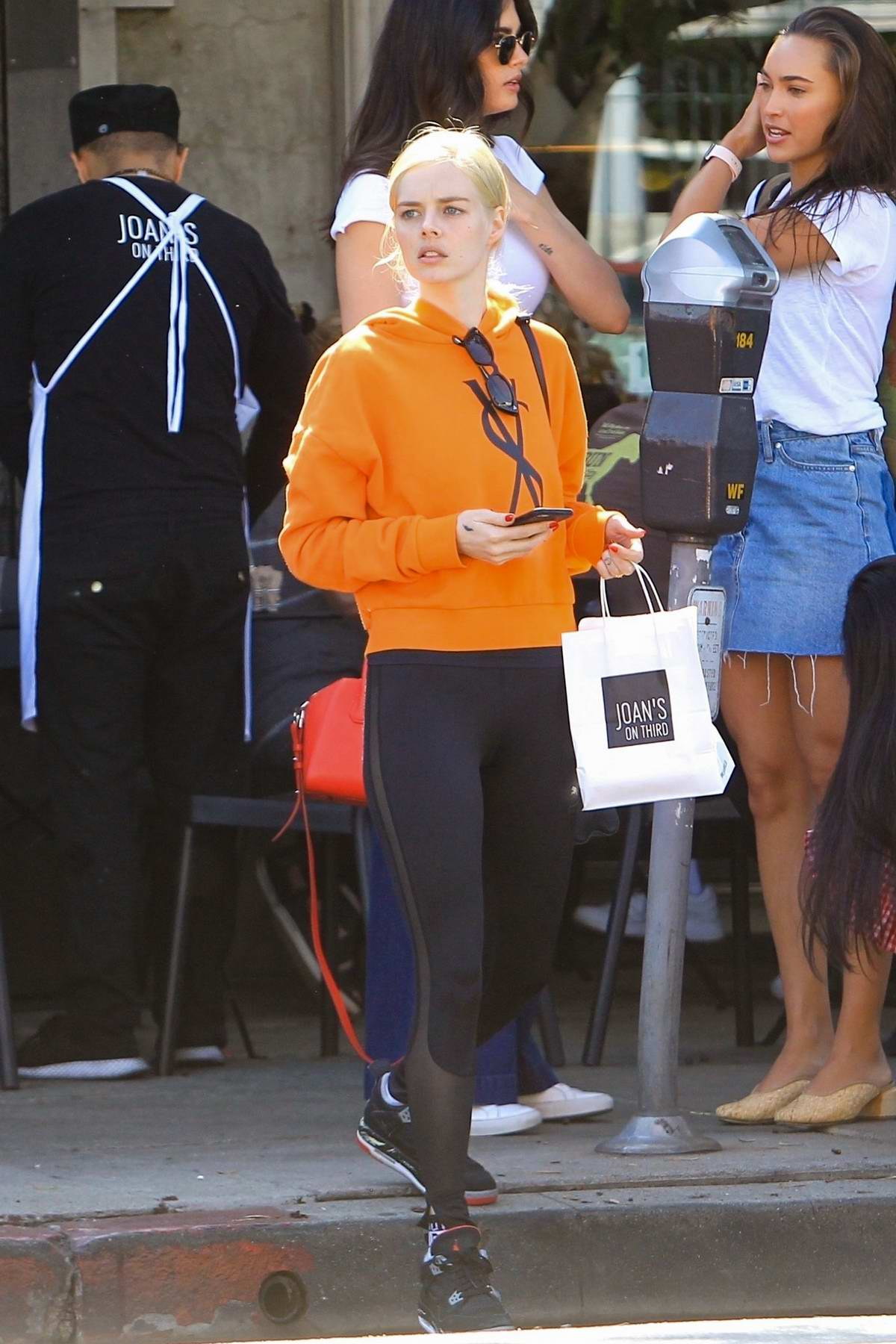 Samara Weaving wears an orange hoodie and black leggings for lunch with friends at Joan's on Third in Los Angeles