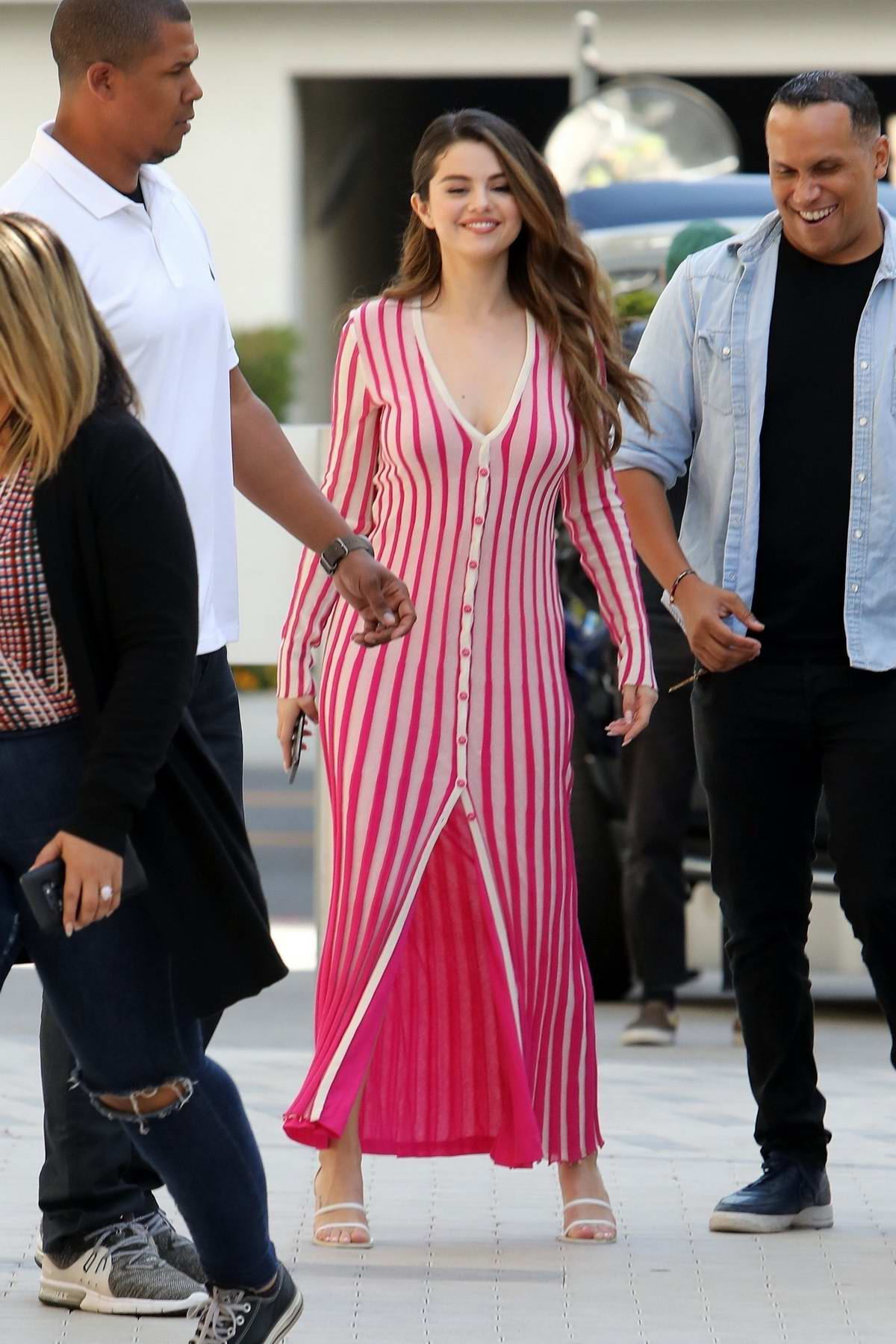 Selena Gomez looks gorgeous in a striped pink dress while out promoting her new singles in Los Angeles