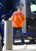 Selena Gomez looks vibrant in a bright orange hoodie as she arrives for a flight out of JFK Airport in New York City