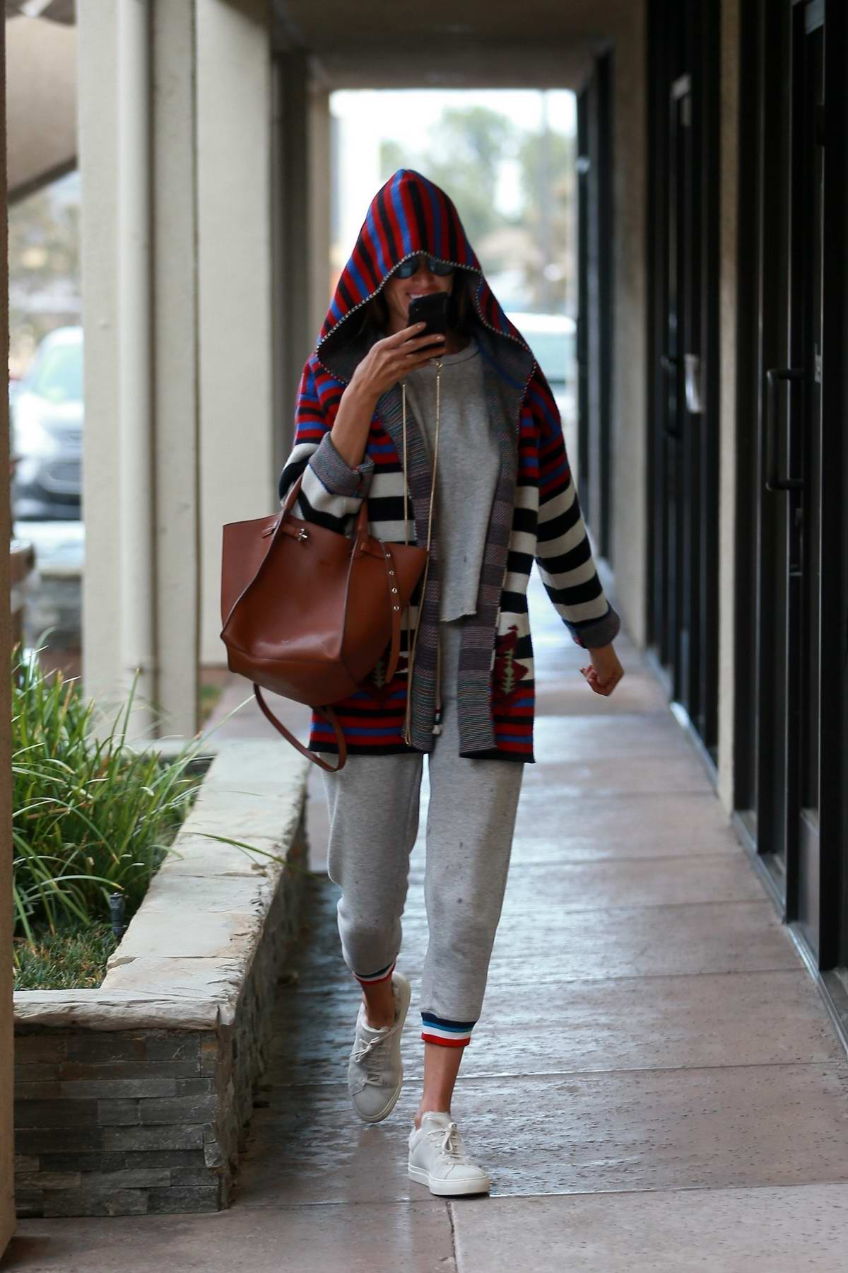 Alessandra Ambrosio braves the rain in a hoodie and grey sweatsuit while arriving at a Facial Clinic in Los Angeles