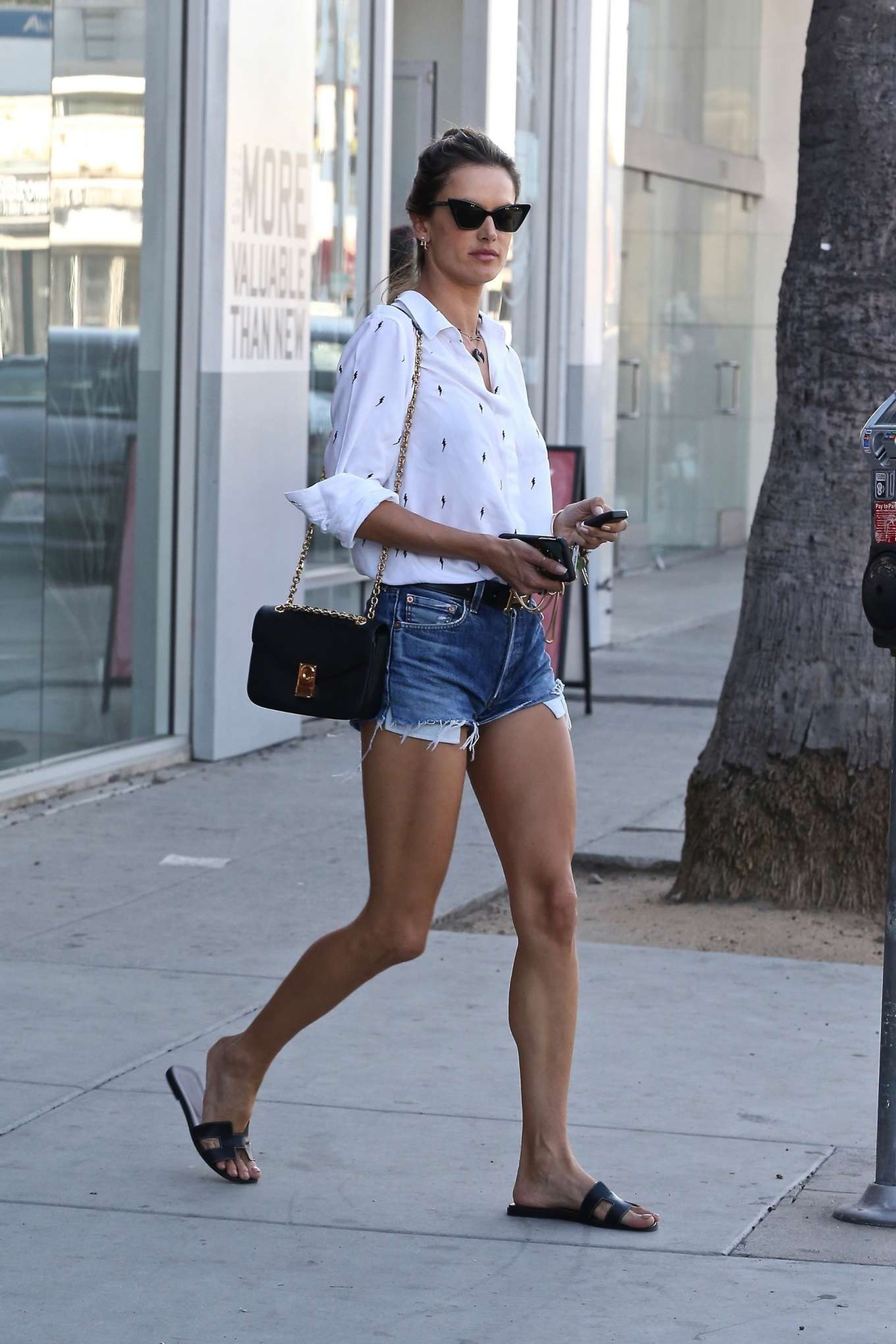 Alessandra Ambrosio rocks denim shorts with a white shirt while shopping for Halloween Costumes in West Hollywood, Los Angeles