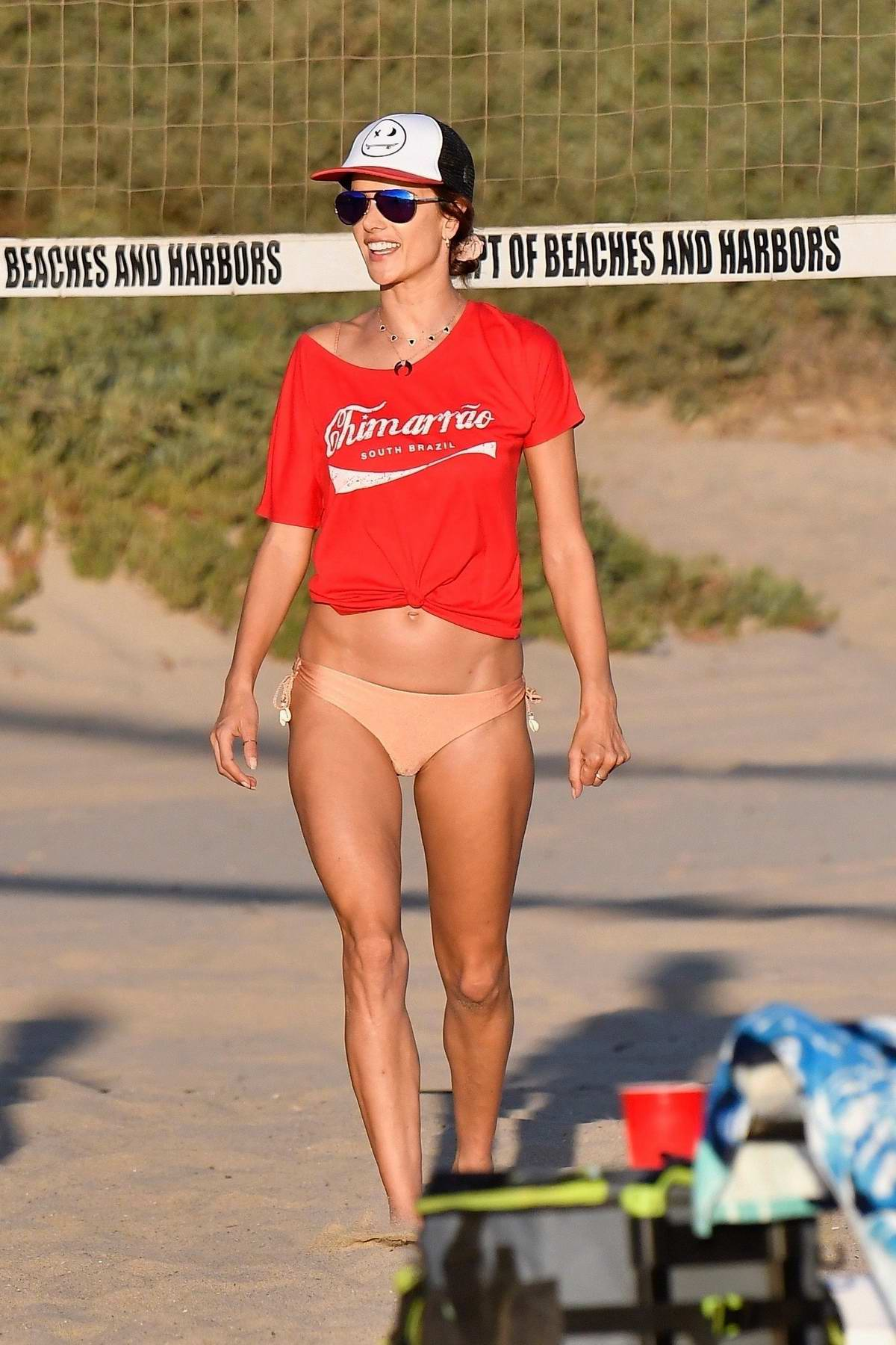 Alessandra Ambrosio wears a red tee and peach bikini bottoms while playing beach volleyball with friends in Santa Monica, California
