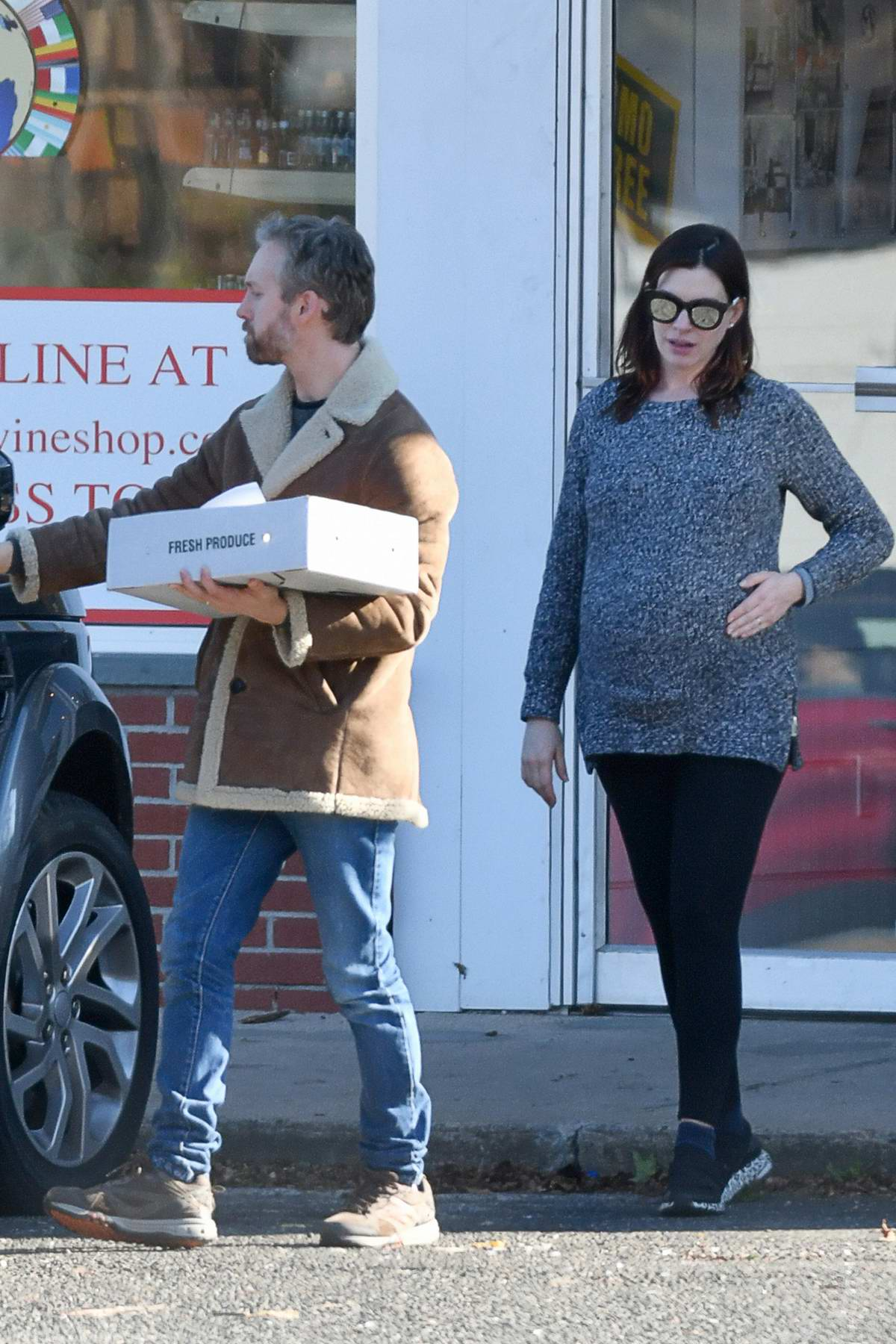 Anne Hathaway cradles her growing baby bump while out with husband Adam Shulman in Westport, Connecticut