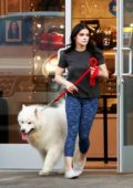 Ariel Winter wears a dark t-shirt and blue leggings while picking up her dogs in Los Angeles