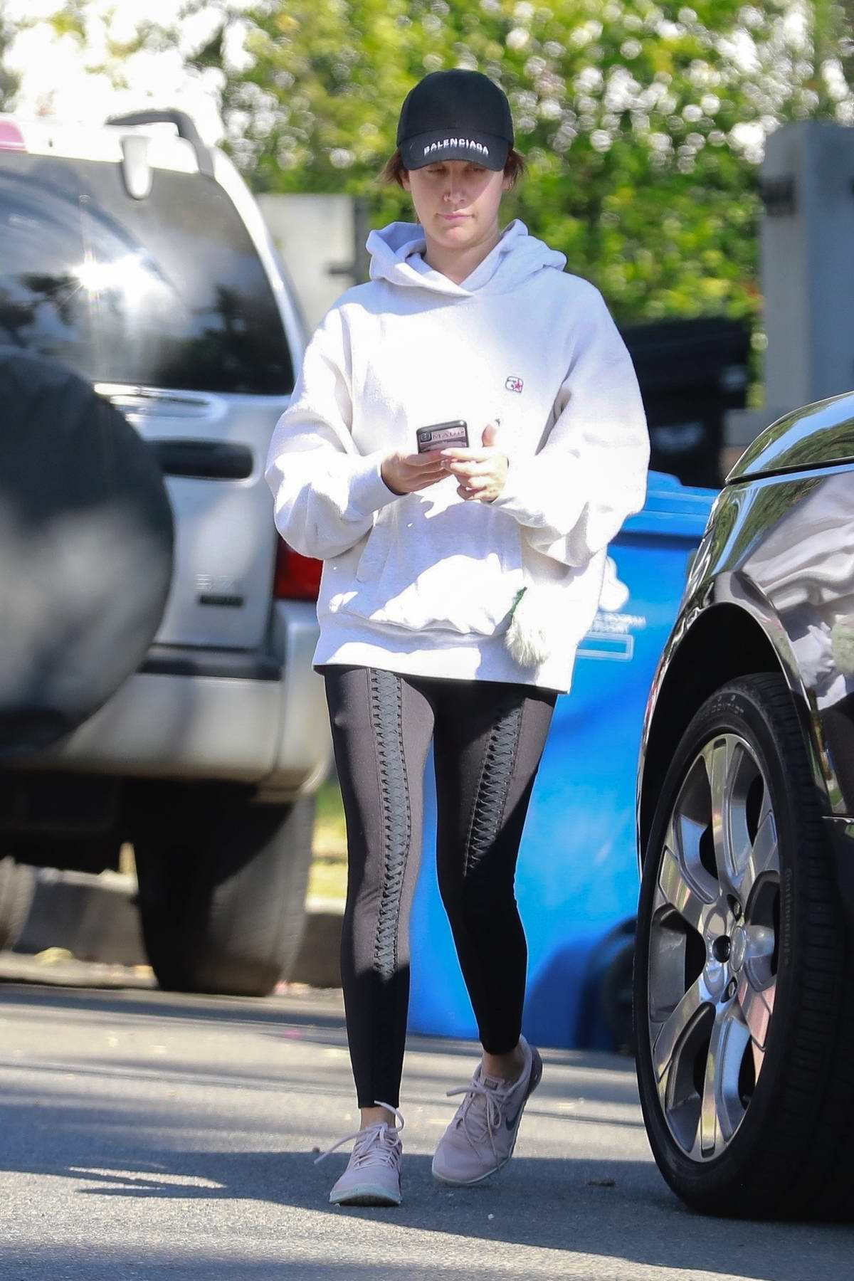 Ashley Tisdale dons white hoodie and black leggings as she leaves a private residence in Los Angeles