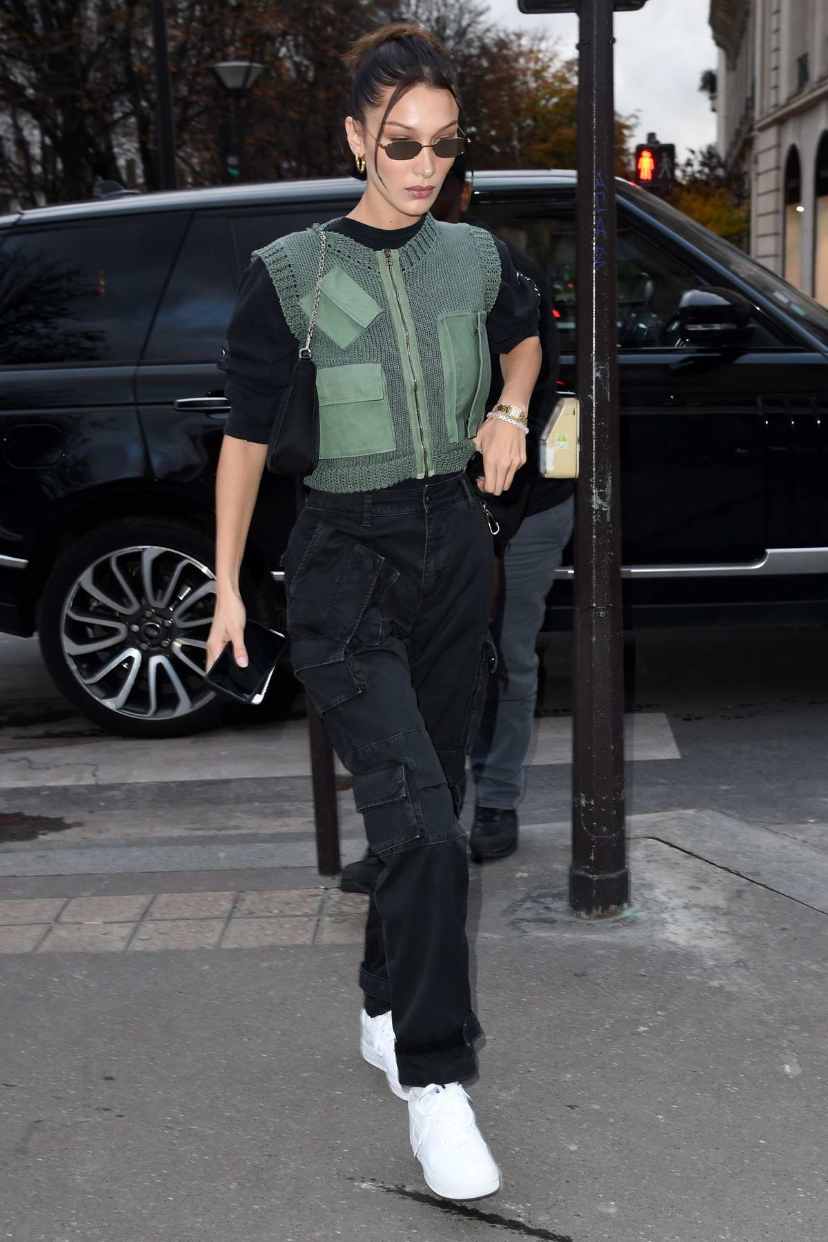 Bella Hadid looks stylish in a green knitted vest with a black top and cargo pants as she steps out in Paris, France