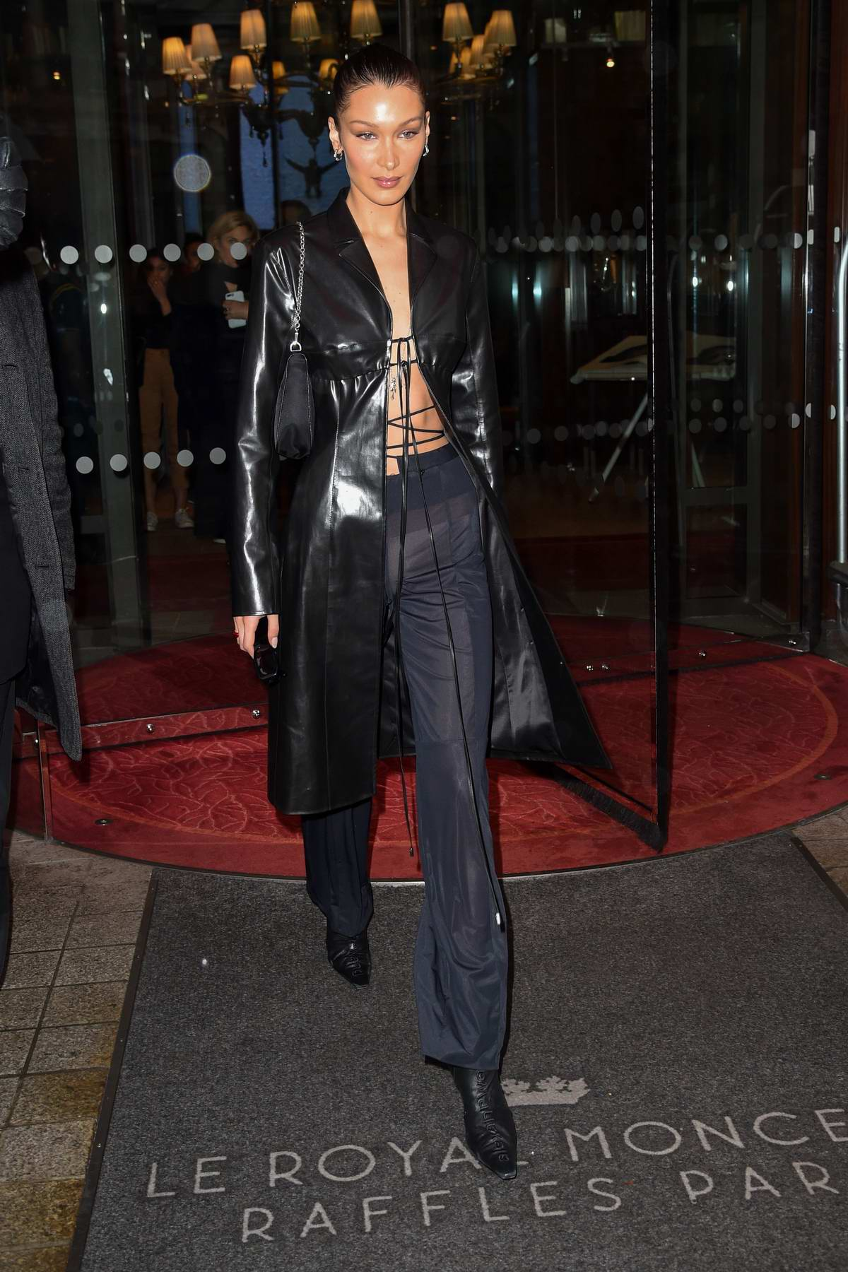 Bella Hadid wears a black leather coat with matching trousers as she leaves her hotel in Paris, France