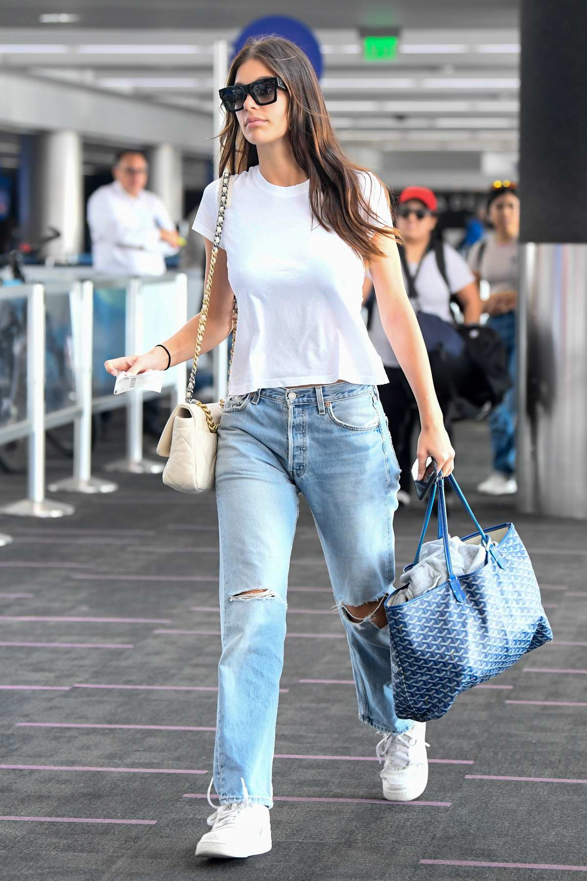 Camila Morrone keeps things casual with a white tee and ripped jeans as she arrives at LAX Airport in Los Angeles