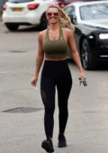 Christine McGuinness wears an olive green workout top and black legging while out at Alderley Edge in Cheshire, UK