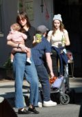 Dakota Johnson carries around her goddaughter while out with Addison Timlin at the Farmer's Market in Los Angeles