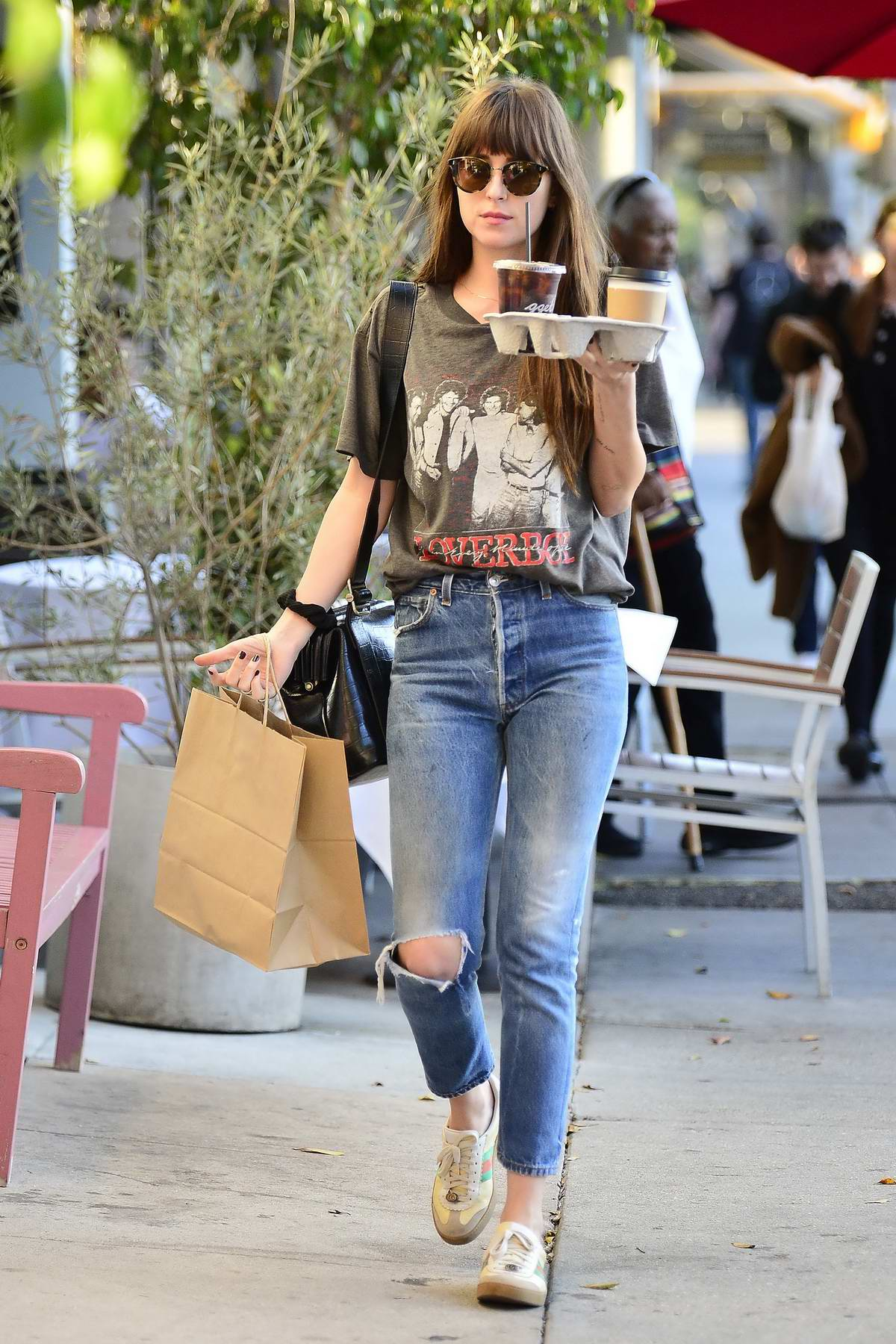 Dakota Johnson rocks 'Loverboy' t-shirt and jeans with Gucci sneakers while making a coffee and snack run in Los Angeles
