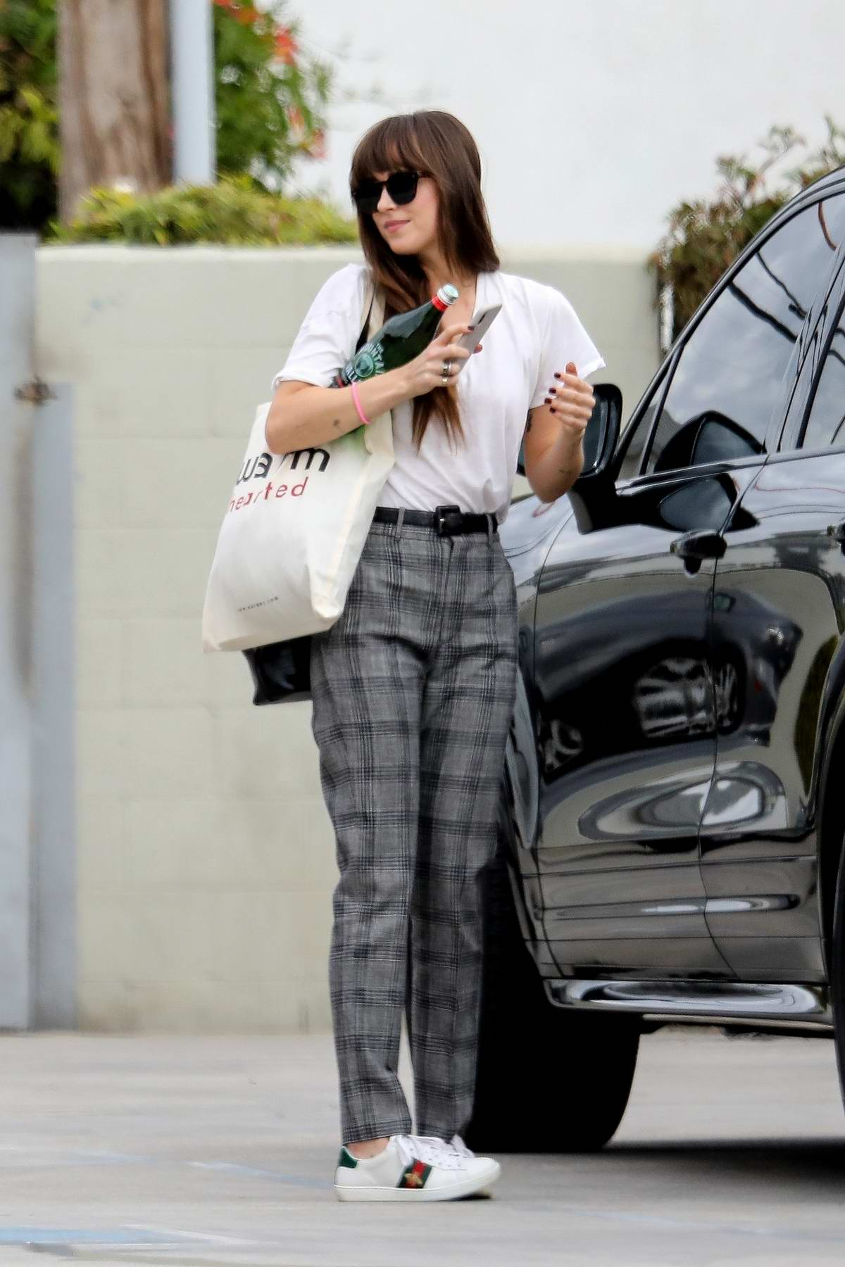 Dakota Johnson wears a white t-shirt with grey plaid pants with Gucci sneakers as she heads to Cabin Editing Company in Santa Monica, California