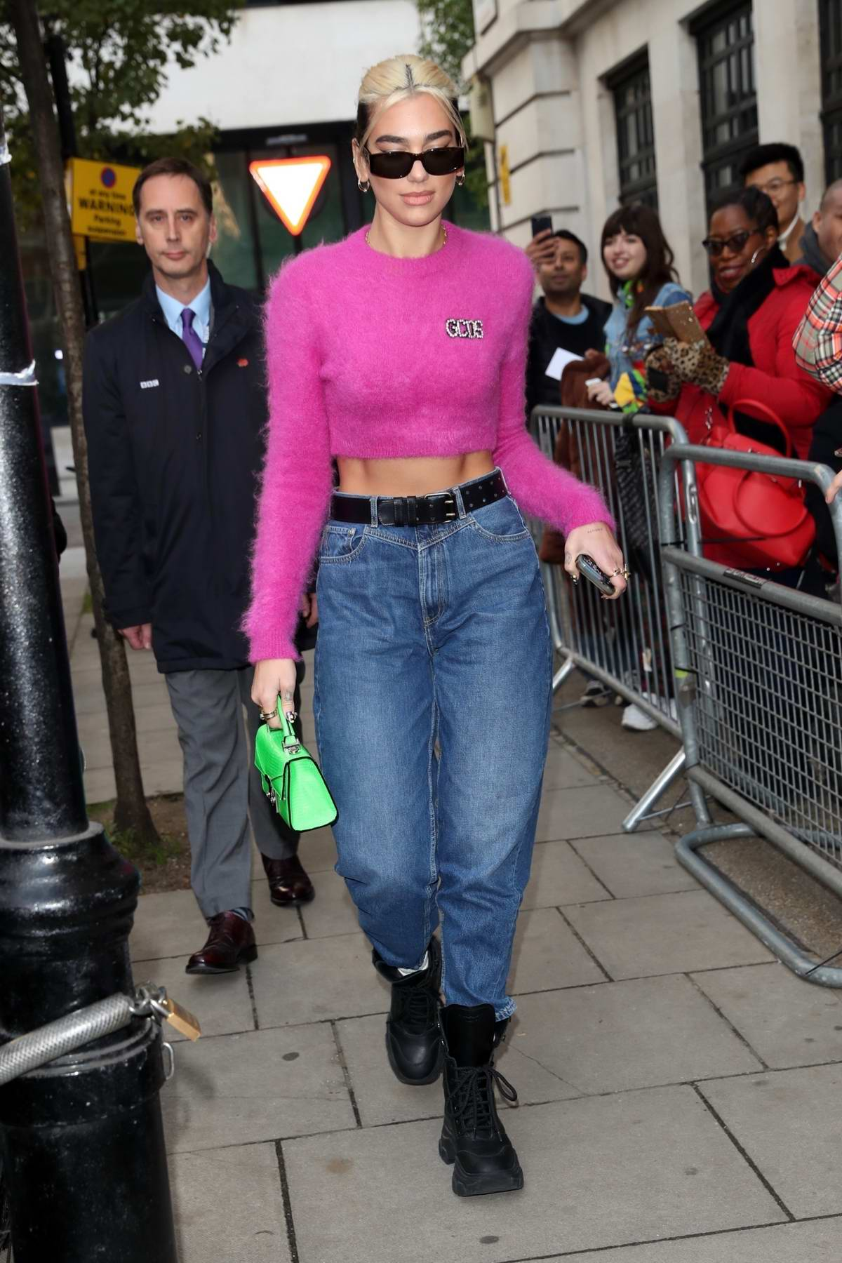 Dua Lipa wears a cropped fuzzy pink sweater and high wasted jeans as she leaves BBC's Zoe Ball Show in London, UK
