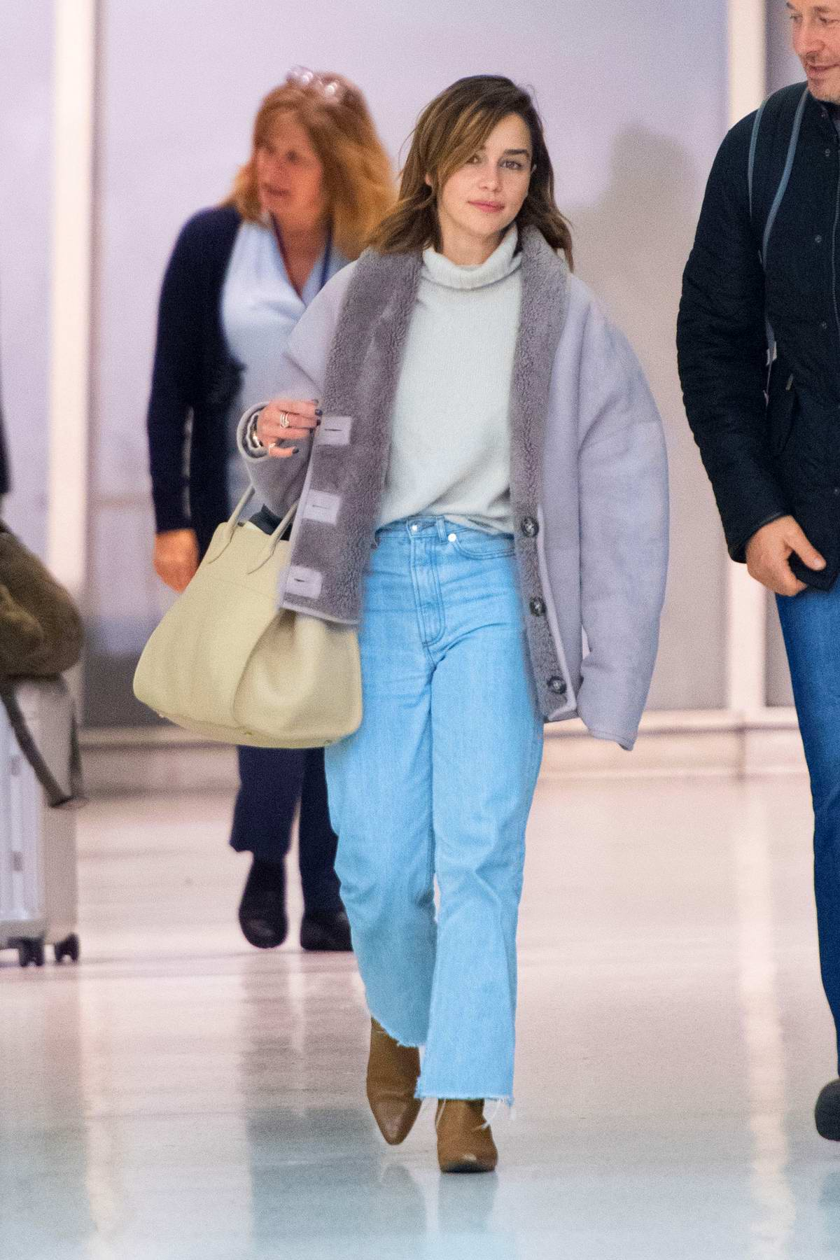 Emilia Clarke is all smiles as she arrives at JFK Airport in New York City