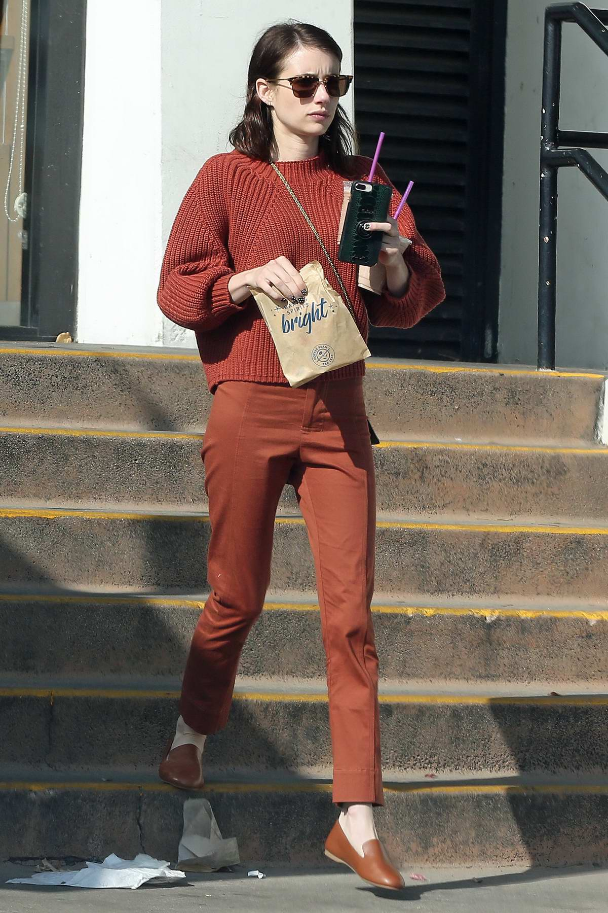 Emma Roberts wears a burnt orange sweater with matching pants and loafers while stepping out in Beverly Hills, Los Angeles