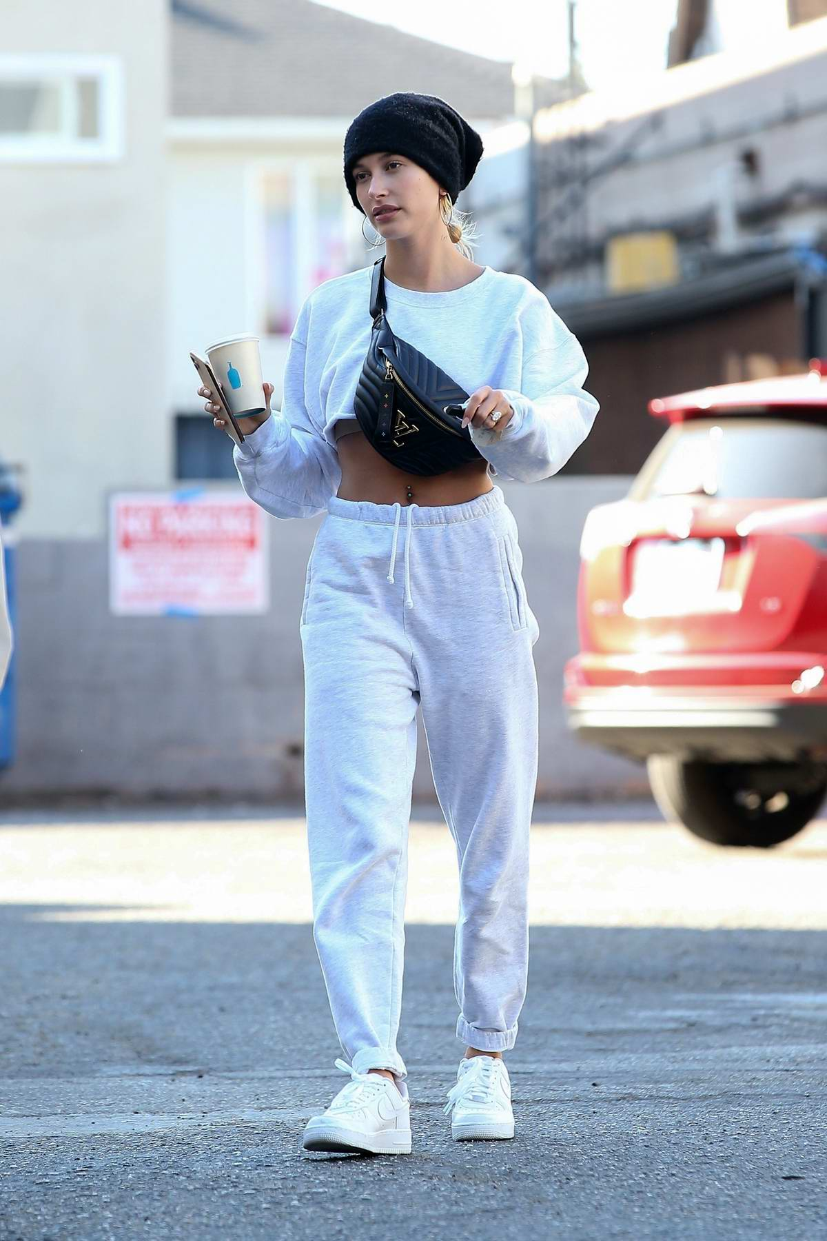 Hailey Bieber sports a cropped white sweatshirt paired with matching sweatpants during a coffee run in Los Angeles