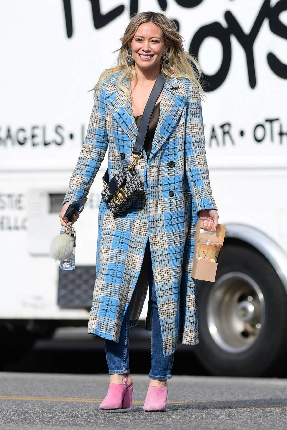 Hilary Duff is all smiles as steps in a blue plaid coat and pink shoes in Los Angeles