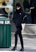 Kaia Gerber bundles up in a black jacket with leggings and a beanie as she takes a post-workout stroll in New York City