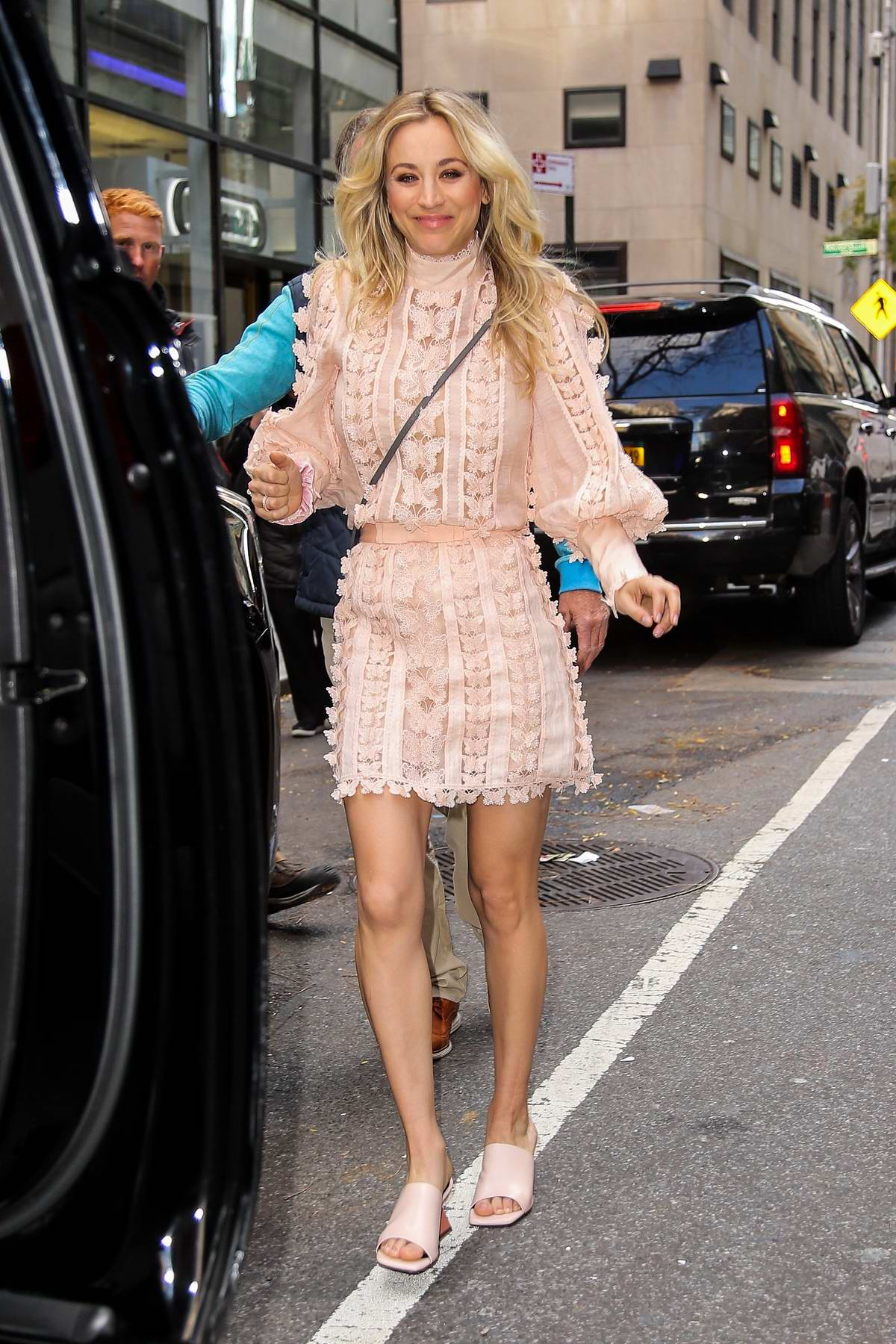 Kaley Cuoco is all smiles as she steps out in a baby pink mini dress in New York City