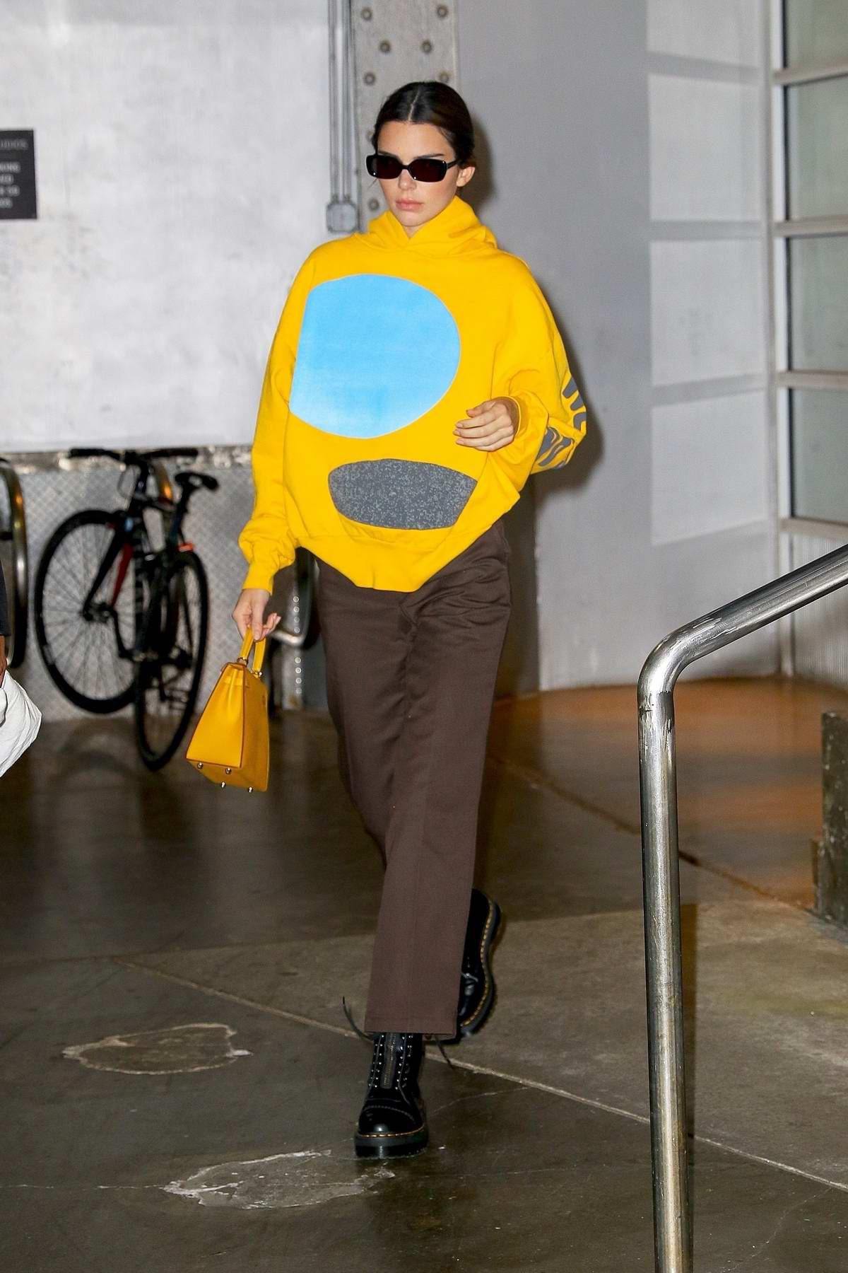 Kendall Jenner seen wearing a bright yellow hoodie as she exits Pier59 Studios in New York City