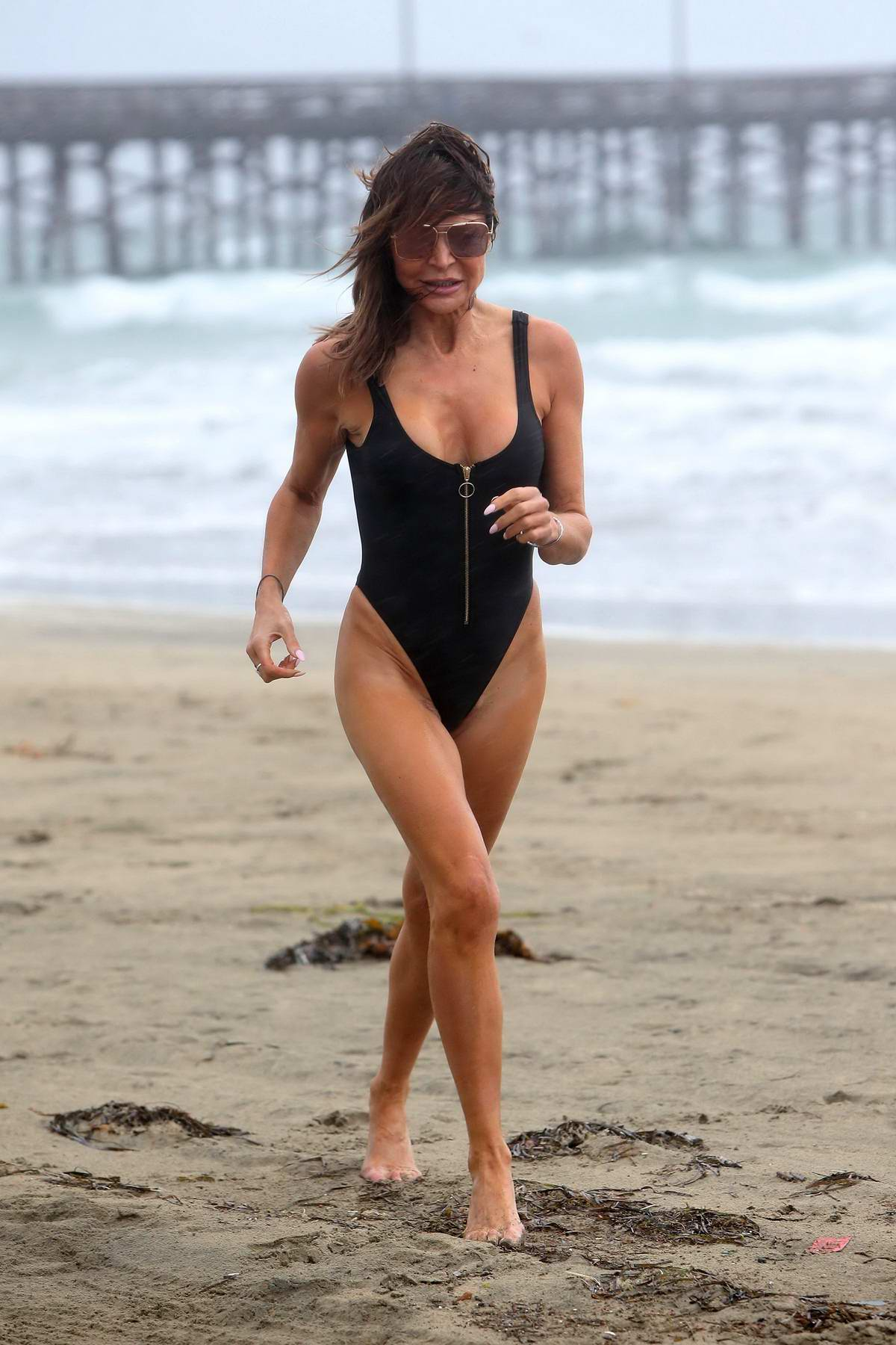 Lizzie Cundy wears a black swimsuit as she hits the beach on a stormy day in Los Angeles