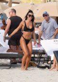 Metisha Schaefer seen wearing a black bikini while enjoying a beach day with friends in Miami Beach, Florida