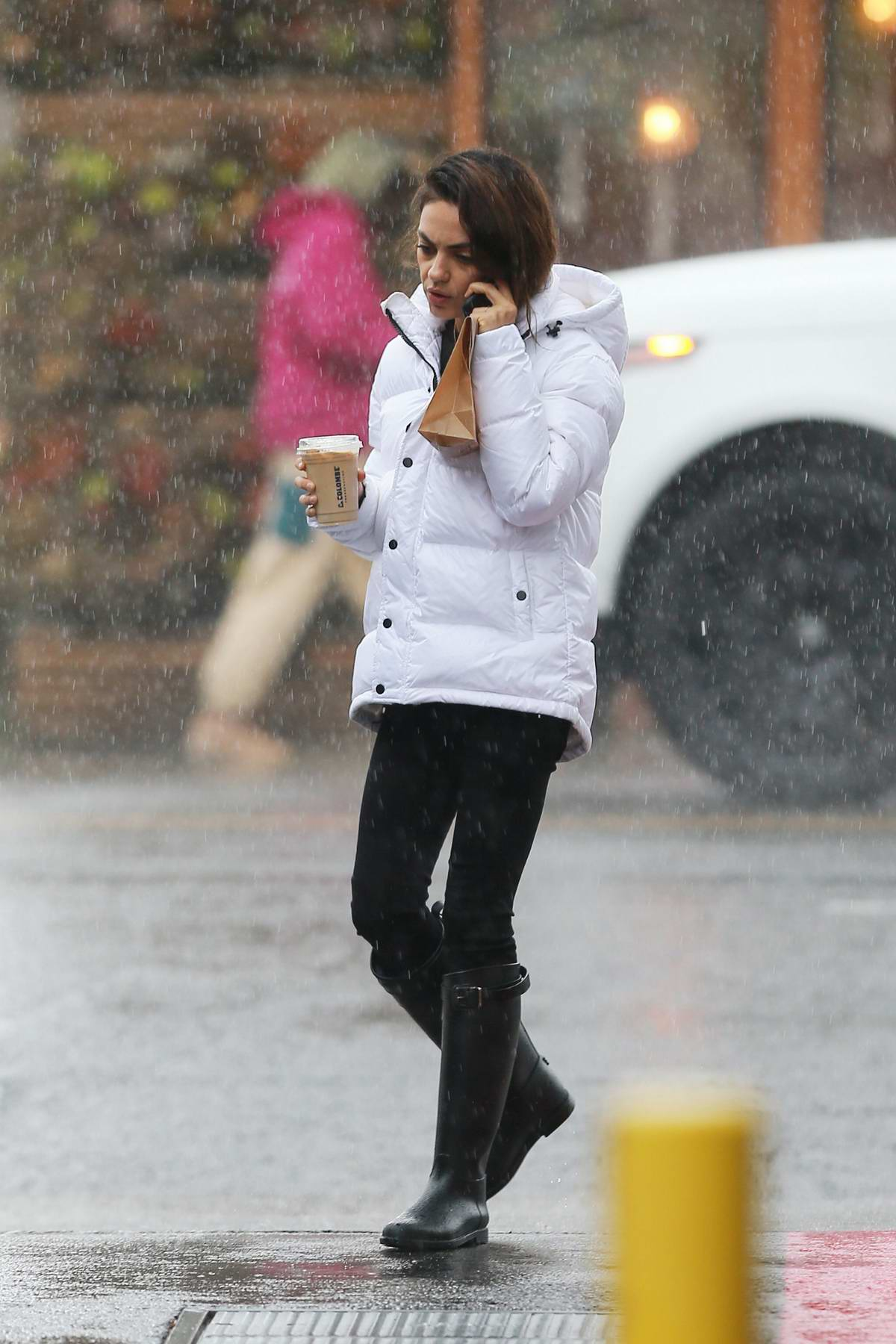 Mila Kunis wears a white parka as she steps out in the rain for some coffee in Los Angeles