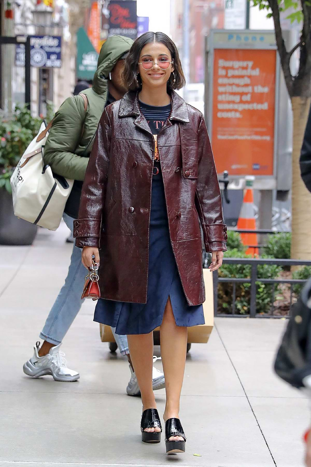 Naomi Scott seen wearing a burgundy leather coat while out in Midtown in New York City