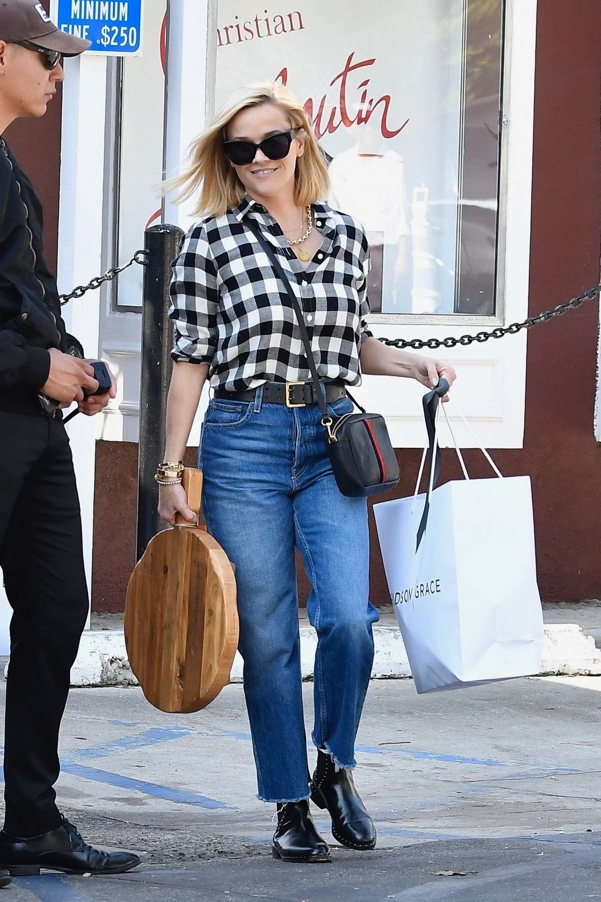 Reese Witherspoon wears a plaid shirt and jeans as steps out for some Christmas shopping in Brentwood, California