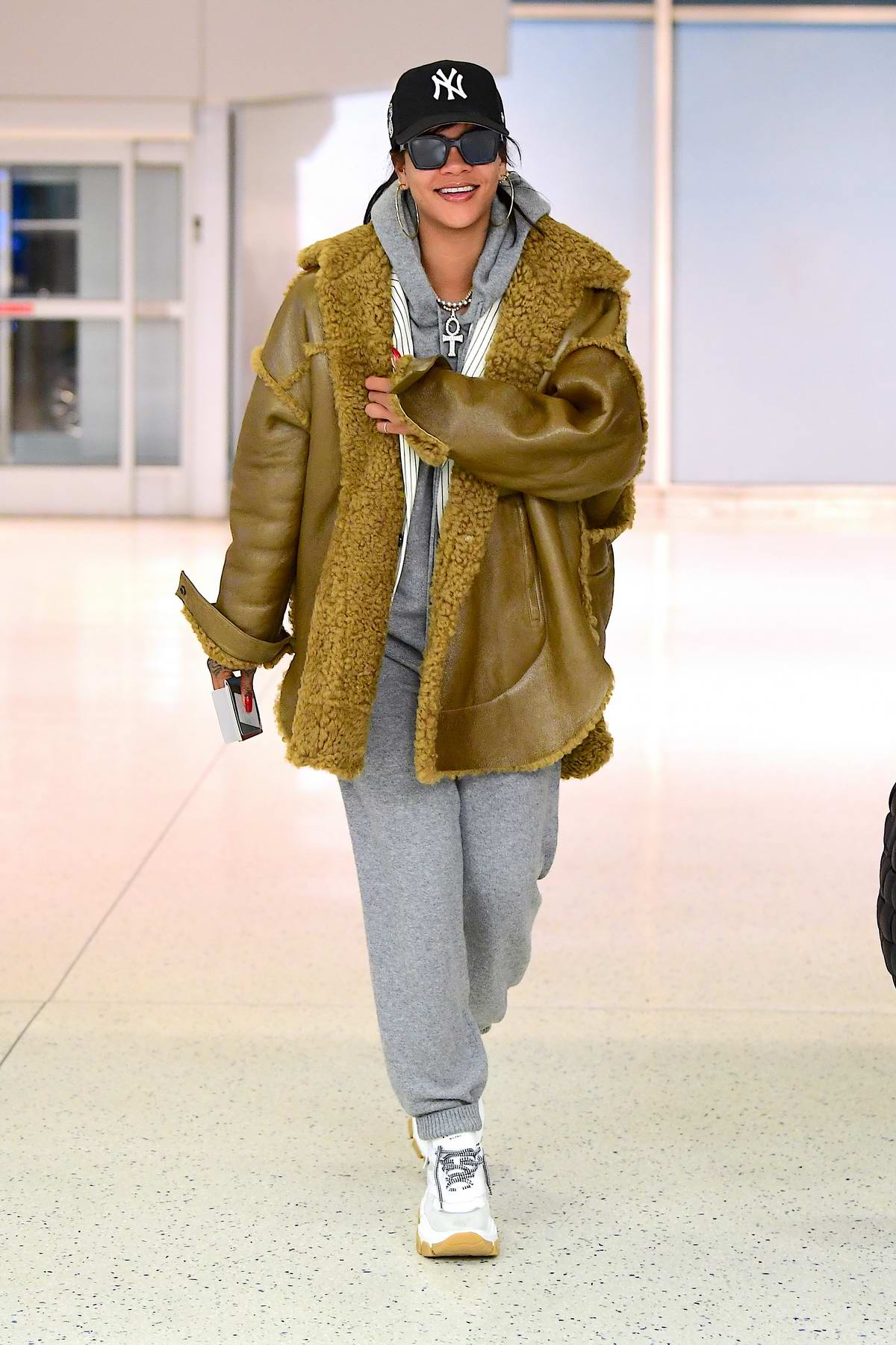 Rihanna seen wearing grey sweatsuit with her Fenty jacket as she arrives for a flight out of JFK airport in New York City