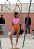 Shanina Shaik poses in a pink top and orange bikini bottoms during a P.E. Nation photoshoot on Venice Beach, California