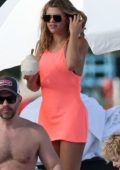 Sofia Richie wears a coral pink dress over her bikini while relaxing at the beach with Scott Disick in Miami, Florida