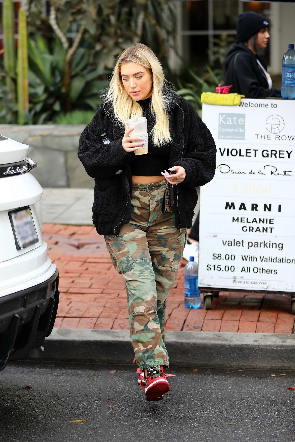 Anastasia Karanikolaou wears a black fleece and camo pants as she grabs an iced coffee at Alfred's in Los Angeles