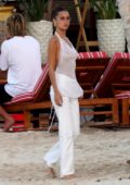 Bella Hadid rocks a white sheer top while at the beach with friends in St. Barts, France