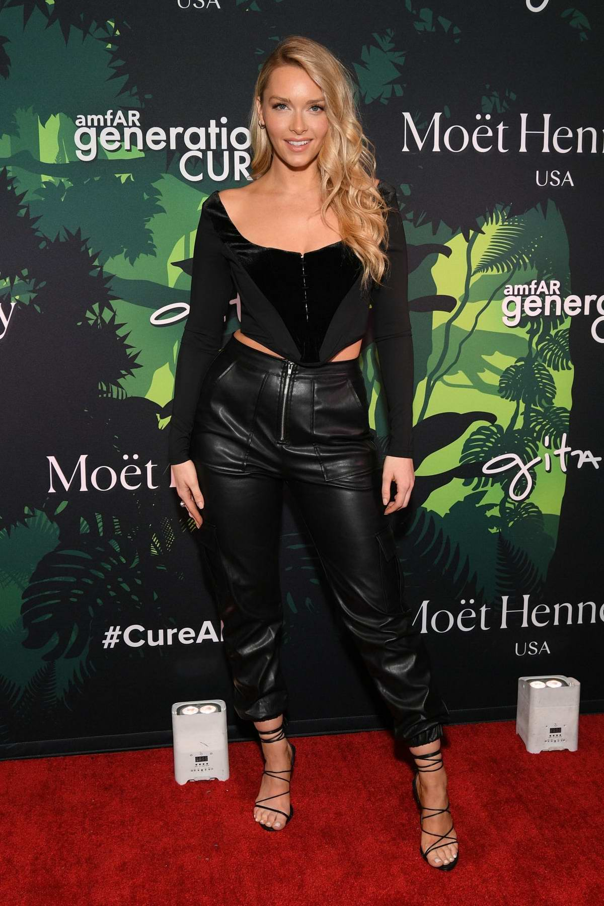 Camille Kostek attends the amfAR generationCURE Holiday Party in New York City