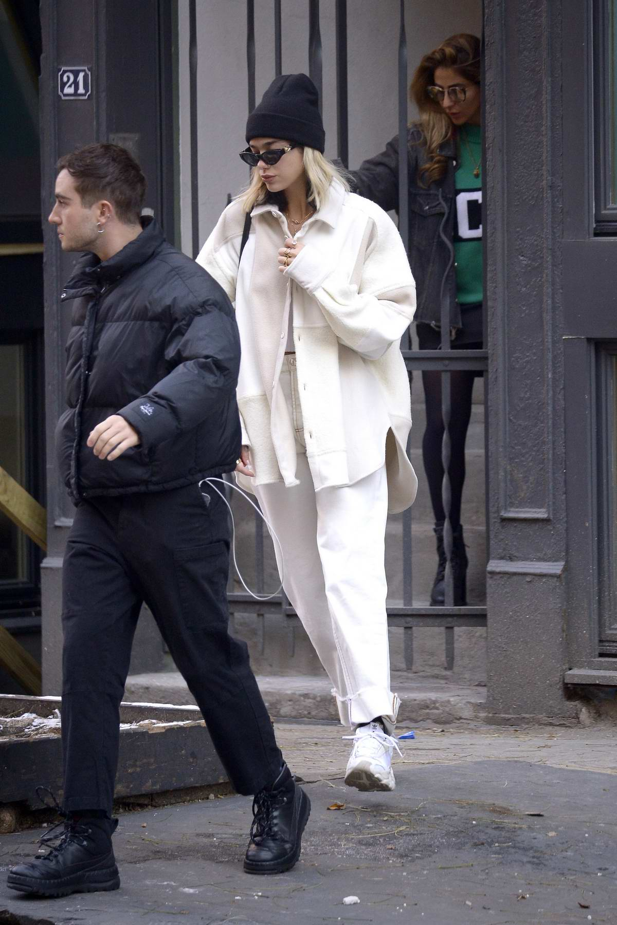 Dua Lipa wears a white coat with matching trousers as she steps out in New York City