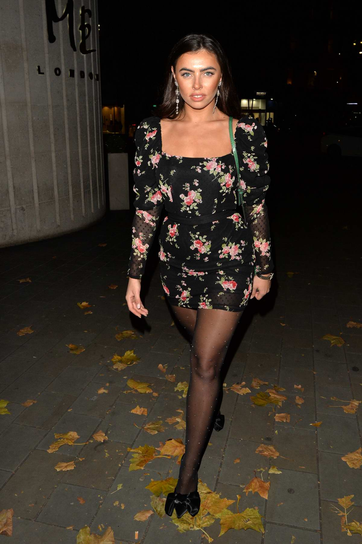 Francesca Allen wears a floral print black mini dress during a night out with friends at STK in London, UK