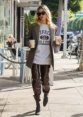 Hailey Bieber looks super chic in a beige blazer and brown leather pants while making a coffee run in Beverly Hills, California